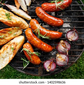 Grilled food, pork sausages, baguette toasts and onion on  grill plate, outdoors, top view. Barbecue, bbq