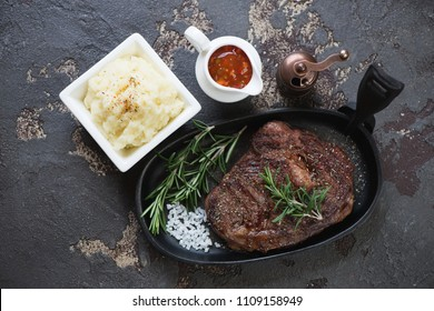 Grilled free-range beef steak with mashed potato and sauce on a brown stone background, horizontal shot, view from above