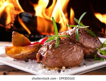 Grilled fresh Beef Steak with flames. Delicious beef steaks with fresh vegetable and trimmings on wooden table.