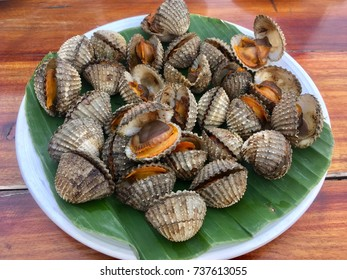 Grilled fresh cockles serve on banana leaf and put on the wooden table