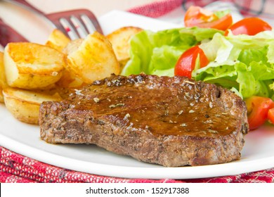 Grilled fried meat beef with roasted golden potatoes and fresh salad with cherry tomatoes