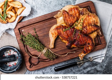 Grilled fried roast Chicken tobacco on cutting board with potato on gray background