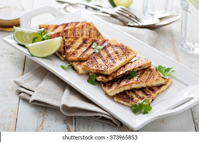Grilled fried tofu  on a plate with sesame and greens