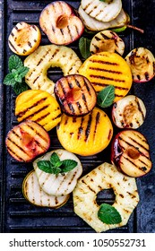 GRILLED FRUITS. Grill fruits - pineapple, peaches, plums, avocado, pear on black cast iron grill board.