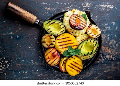 GRILLED FRUITS. Grill fruits - pineapple, peaches, plums, avocado, pear on black cast iron grill pan. Dark background. Top view.