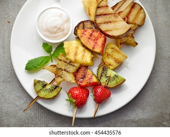 grilled fruits on wooden skewers and yogurt sauce, top view