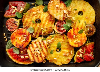 Grilled fruits; pineapples, peaches, figs, pears and watermelon with pine nuts, fresh herbs and honey on the grill plate, top view. Gourmet fruit dessert