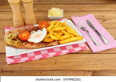 Grilled gammon egg and chips meal on a white plate with tomatoes and pineapple ring
