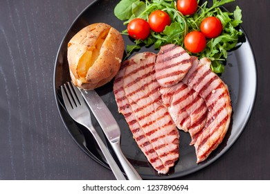 A grilled gammon steak with a baked potato and salad