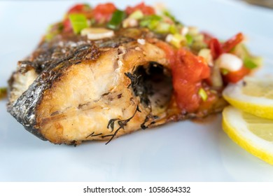 Grilled Gilt Head Bream or Sea Bream fish on a white plate with lemons.
