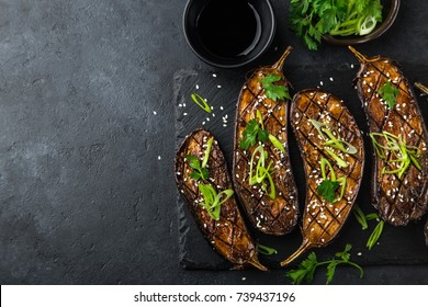grilled glazed eggplants on black background, top view, copy space