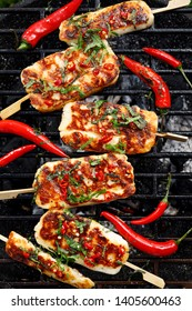 Grilled halloumi cheese with the addition of mint and chilli pepper while grilling outdoors, top view.  Delicious, vegetarian, grilled snack
