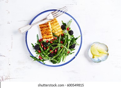 Grilled Halloumi Cheese with Blackberry, Pomegranate Seeds and Fresh Rocket. Home made food. Concept for a tasty and healthy meal. White wooden background. Top view. Copy space.