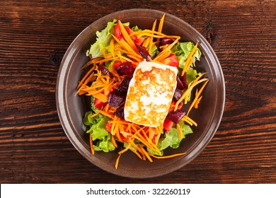 Grilled halloumi cheese with colorful fresh salad on plate on wooden table, top view. Culinary delicious vegetarian eating, mediterranean style.