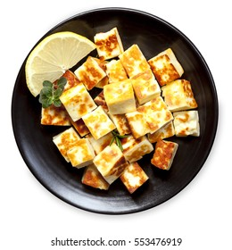 Grilled halloumi cheese cubes with lemon and herbs.  On black plate, top view, isolated on white.