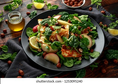 Grilled Halloumi Cheese salad with peach fruit, nuts and spinach, arugula mix. healthy food