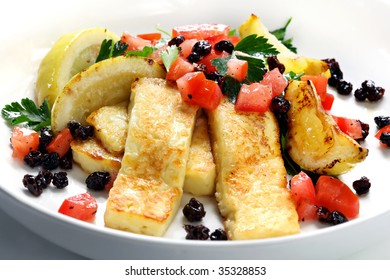 Grilled halloumi cheese with a salad of tomatoes, currants and parsley.  With grilled lemon wedges.  Popular in Greece, Cyprus, Turkey, and the Middle East.