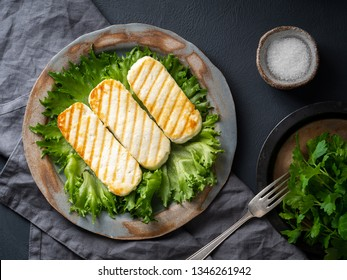 Grilled Halloumi, fried cheese with  lettuce salad.  Balanced diet on  dark background, top view
