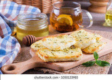 Grilled haloumi cheese with herbs and honey on a cutting board