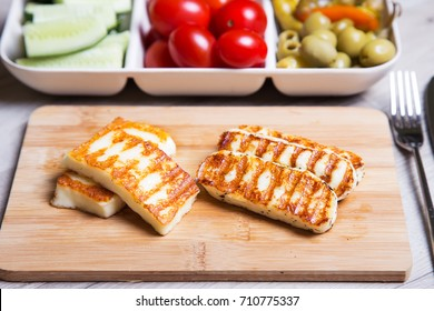 Grilled haloumi cheese on a wooden board with olives, cherry, cucumbers and pepperoni. Close-up. Selective focus