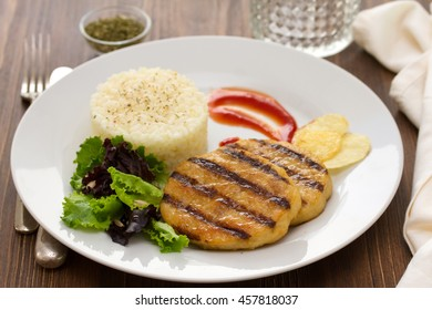 grilled hamburger with rice, salad and chips on plate