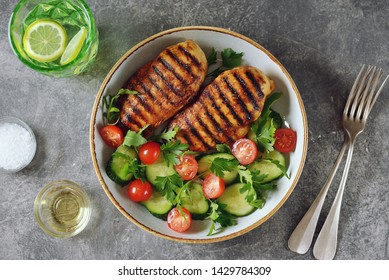 Grilled healthy chicken breast with a salad of cherry tomatoes, cucumbers, arugula and parsley.