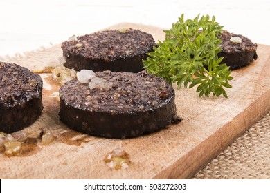 grilled home made irish black pudding with parsley on a wooden board