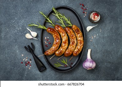 Grilled homemade rosemary sausages skewers on iron frying pan over rustic dark stone kitchen table. Top view, flat lay