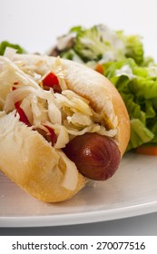 Grilled Hot Dog with sauerkraut and hot red peppers, with side salad