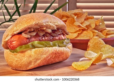 Grilled Hot dog or wiener with fried onions and marinated cucumbers. Potato chips. Ultimate classic fast food.