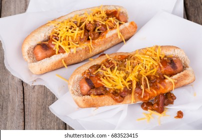 Grilled hot dogs with chili and cheese on a rustic wooden surface