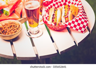 Grilled hot dogs with mustard and ketchup on the table with draft beer.