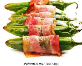 Grilled jalapenos, wrapped in bacon, isolated on white