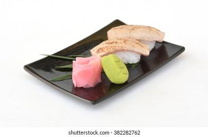 Grilled japanese tuna sushi on black plate, isolated on white background