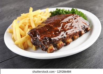 Grilled juicy barbecue pork ribs in a white plate with fries and parsley.
