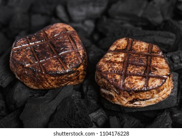 Grilled juicy beef pork steak on barbecue black coil
