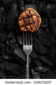 Grilled juicy beef pork steak on barbecue black coil with fork