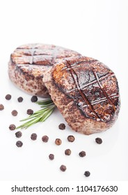 Grilled juicy beef pork steak slice on white background with pepper and rosemarine herb
