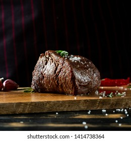 Grilled juicy beef steak served on wooden table with salt, spices and herbs. Dark background, copy space menu.