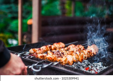 Grilled kebab cooking on metal skewer. Roasted meat cooked at barbecue. BBQ fresh beef meat chop slices. Traditional eastern dish, shish kebab. Grill on charcoal and flame, picnic, street food