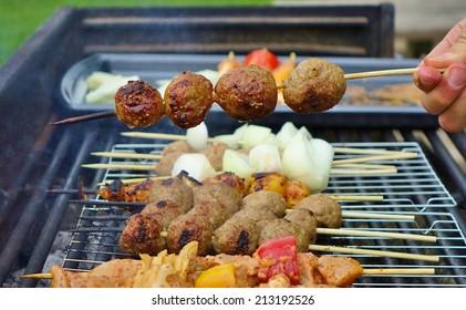 Grilled Kibbeh (Kibbeh Kebab) skewers on the grill.