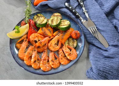 Grilled king prawns with mixed mediterranean vegetables served on a blue plate on a table with concrete look