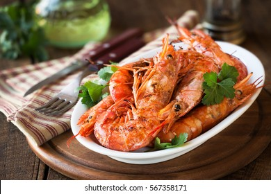 Grilled King prawns or shrimps with parsley on white plate on dark rustic wooden table
