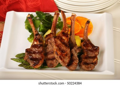 Grilled lamb chops with asparagus and sliced oranges.
