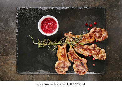 Grilled Lamb Chops with Cranberries and Rosemary on Natural Black Stone Background. Roasted Cutlets on Creative Restaurant Backdrop. Mutton Ribs with Spices and Sause Top View