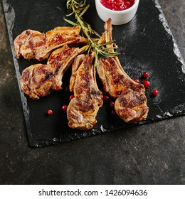 Grilled Lamb Chops with Cranberries and Rosemary on Natural Black Stone Background. Roasted Cutlets on Creative Restaurant Backdrop. Mutton Ribs with Spices and Sause