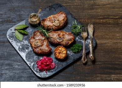 Grilled Lamb Chops with herbs on Black Stone on Dark Old Wooden Background