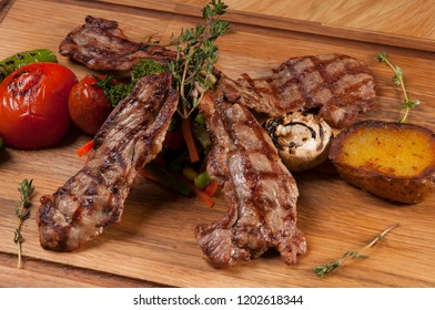 grilled lamb chops on wooden serving board with tomato, potato and rosemary