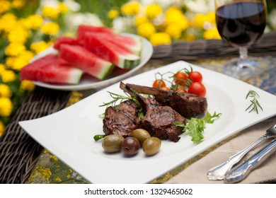 Grilled lamb chops served with cherry tomatoes and olives. Watermelon and wine. Outside dinner in a garden.