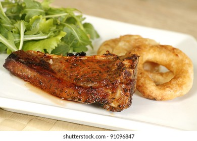 grilled lamb cutlet with onion rings and rocket lettuce